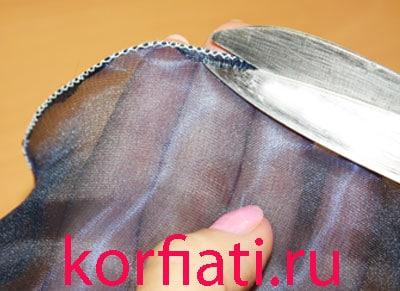 Обрезать лишнюю ткань из под края волана